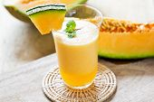 picture of cantaloupe  - Cantaloupe smoothie in a glass by fresh cantaloupe - JPG