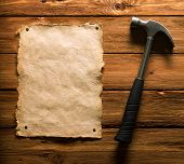 Hammer And Old Paper On Wood