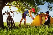Young couple setting up a tent on a green meadow under big oak