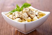 Cubed feta cheese on wooden cutting board
