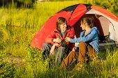 Camping los adolescentes beben cerveza al aire libre al atardecer en la pradera