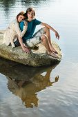 Couple sitting on rock by lake sharing romantic moment