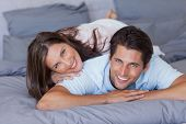 Lovely couple smiling at camera and lying on bed