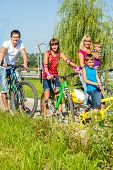 Family on bikes in a summer park
