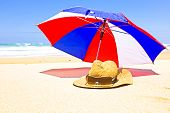 Straw hat, sunglasses and parasol at the beach