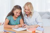 Smiling mother helping daughter with homework in living room