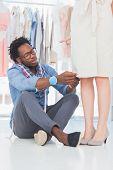 Modedesigner sitzen und verlegen von Nadeln auf Kleid
