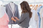 Fashion designer measuring blazer in a bright office