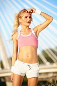 Sporty fitness woman outdoor workout. Young runner woman smiling happy resting after jogging trainin