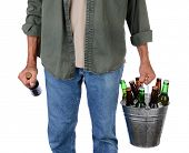 Closeup of a man in jeans carrying a bucket of beer in one hand and a single bottle in the other. Man is unrecognizable, torso and legs only, isolated on white.