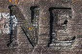 N And E Carved Into Lichen Covered Board
