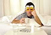 image of hangover  - exhausted young Man in bed with coffee water and tablets suffering hangover and headache - JPG