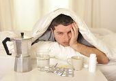 Man With Headache And Hangover In Bed With Tablets