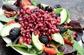 stock photo of pomegranate  - A healthy salad with pomegranate avocado tomatoes almonds and argula lettuce over a rustic background - JPG