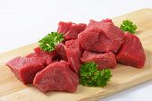 heap of diced beef meat with pieces of parsley, served on the wooden cutting board