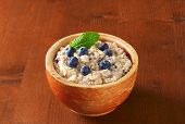 bowl of oatmeal with fresh blueberries, on the wooden table
