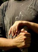 hands of gardener holding haft of spade
