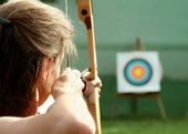 stock photo of bow arrow  - Archer spans the bow and aims to target.