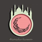 Arabic Islamic calligraphy of text Ramadan Kareem in crescent moon shape with mosque on grey background.