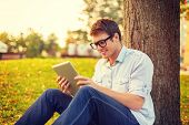 education, technology and internet concept - smiling male student in eyeglasses with tablet pc outside