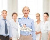 business and money concept - smiling businesswoman with dollar cash money