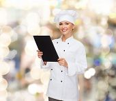 cooking, advertisement and food concept - smiling female chef, cook or baker with blank black menu paper