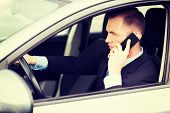 transportation and vehicle concept - man using phone while driving the car