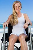 Wheelchair bound blonde sitting on the beach smiling at camera on a sunny day