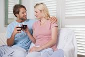 Happy couple sitting on couch with red wine at home in the living room