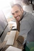 Cheerful guy sitting in front of desktop computer