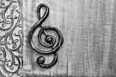 Black and white photo of metal treble clef on distressed wood with decorative carved border.   Close