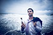 Businessman by the Beach with Message in a Bottle