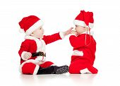 Two Funny Small Kids In Santa Claus Clothes Isolated On White Background