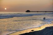 Sunset At The Pier In Oceanside Beach, California. One Surfer Going In The Water.
