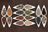 Healthy seed food selection in white porcelain bowls over lokta paper background..