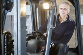 Experienced forklift driver is posing inside his forklift in a warehouse