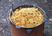 pic of cauldron  - Cooking pilaf in a large cauldron outdoors - JPG