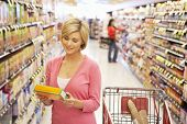 stock photo of grocery cart  - Woman shopping in supermarket - JPG