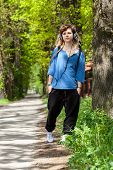 stock photo of dread head  - Rasta girl with dreads walking and listening reggae - JPG