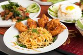 pic of egg noodles  - Thai style fried chicken wings on a round white plate with egg noodles and spinach - JPG