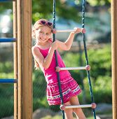 cute  happy little girl on outdoor playground equipment