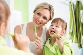 picture of bathing  - mother and child daughter brushing teeth in bathroom - JPG