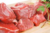 uncooked fresh beef meat chunks on wooden cutting plate with green hot and red peppers isolated over