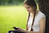 Teen Girl Sitting Near Tree With Mobile Phone