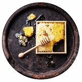 Honeycomb With Wooden Honey Dipper On White Background