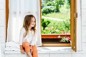 Cute Little Girl Sitting On A Bathroom Window