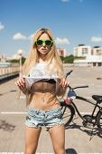 image of swag  - Young woman standing next to black bicycle - JPG