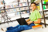 Smiling pupil with books and laptop in library