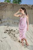 Señora en un vestido rosa escamoso en la cantera de arena