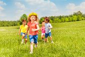 Happy running kids in green field during summer